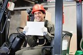 stock photo of forklift driver  - Portrait of happy young forklift driver displaying blank placard - JPG
