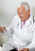 Happy senior male radiologist in lab coat reviewing ultrasound print
