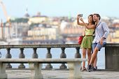 Europe travel. Romantic couple tourists in Stockholm taking selfie photo having fun enjoying skyline view and river by Stockholms City Hall, Sweden.