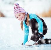 happy  cute little girl in thermal suits sits on the ice in winter outdoors