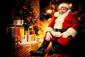 Santa Claus brought gifts for Christmas and sat down to rest by the fireplace. Home decoration.