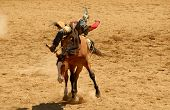 stock photo of bronco  - A Cowboy riding a bucking bronco at a rodeo - JPG
