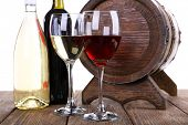 Wine in goblets and in bottles and wooden barrel on wooden table on white background