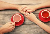 Tea cups and holding hands at the wooden table