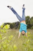 Young man performing handstand in meadow
