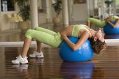 Hispanic woman stretching on exercise ball