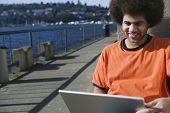 African man looking at laptop on urban pier