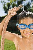Hispanic boy holding hose over head