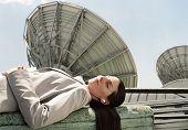 Hispanic businesswoman wearing earbuds next to satellite dishes
