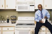 African man eating take out food in kitchen