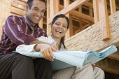 Hispanic couple looking at blueprints at construction site