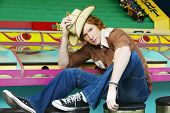 Male teenager with straw hat sitting on stool at carnival booth