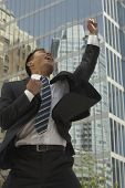 Asian businessman cheering in front of sky scraper
