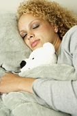 Close up of woman sleeping with teddy bear in bed