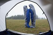 stock photo of sleeping bag  - Indian couple wrapped in sleeping bags at campsite - JPG