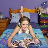 Teenaged girl reading in bedroom