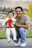 Hispanic father holding baby in costume