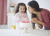 Hispanic girl celebrating birthday with mother