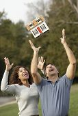 Hispanic couple throwing model of house in air