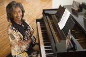 Senior African woman sitting at piano