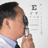 Asian male optometrist looking through medical instrument