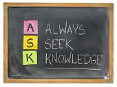 ASK acronym - always seek knowledge - sticky notes and chalk writing on a blackboard