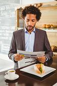 Businessman reading newspaper while having lunch at the coffee shop