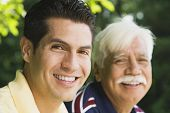 Hispanic man smiling with father outdoors