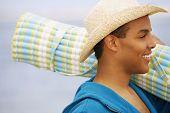 Hispanic man carrying beach mat