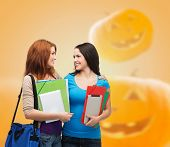 education, holidays, school, friendship and people concept - smiling student girls with books and bag over halloween pumpkins background