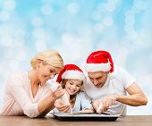 food, family, christmas, happiness and people concept - smiling family in santa helper hats with glaze and pan cooking over blue lights background