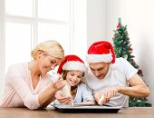 food, family, happiness and people concept - smiling family in santa helper hats with glaze and pan cooking over living room and christmas tree background