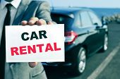 a man in suit holding a signboard with the text car rental written in it and a car in the background