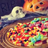 a pile of different Halloween candies with scary ornaments in the background, such a tombstone, a skull, a pumpkin and cobwebs