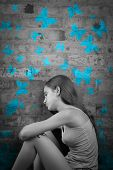 Sad teenage girl in black and white with blue butterflies painted on a brick wall