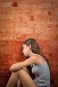 Sad and lonely teenage girl sitting on the floor against a brick wall
