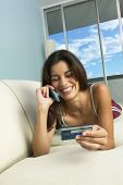 Hispanic woman laying on sofa using cell phone with credit card