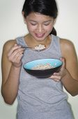 Portrait of Asian woman eating cereal