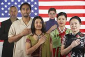 Multi-ethnic people standing in front of American flag