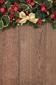 Christmas background border with red bauble decorations, fir, holly and cedar cypress with pine cones over old oak wood.