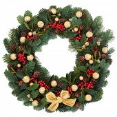 Christmas and winter wreath with gold bauble decorations,holly, ivy, mistletoe, spruce fir and pine cones over white background.