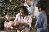 Hispanic family opening gifts on Christmas