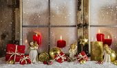 Atmospheric and romantic classical christmas window decoration with red candles, snow and wood in white, red and golden colors.