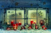 Old wooden window decorated for christmas with red candles and gift boxes for a greeting card.