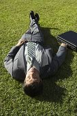 South American businessman laying in grass