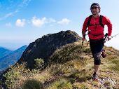 Skyrunner runs uphill along a mountain ridge. Front view, caucasian man. Sunny summer day. West Alps, Europe.