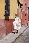 Hispanic girl on sidewalk in Quinceanera dress