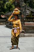 SEPTEMBER 18, 2014 - BALI, INDONESIA: A Balinese lady carries a straw basket on her head walks into the Tirta Empul Temple for ceremonial prayers.  Hinduism is the religion of the Balinese people.