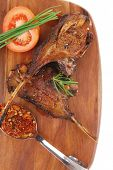 meat over wood: grilled ribs on plate with tomatoes and spices isolated on white background