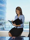 Hispanic businesswoman writing in folder